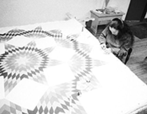 A stitch in time: Marlene Roulliard works on a star quilt  in the Four Winds basement.