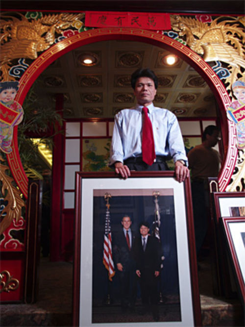Dan Tang in 2004, with his photo of George Bush.