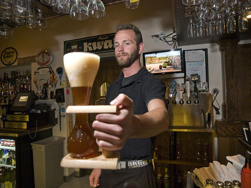 Kyle Kainz delivers a beer at the Cheeky Monk, Denver's only Belgian cafe. See more photos at westword.com/slideshow.