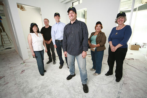 Aaron Miripol (center) and his crew from Urban Land Conservancy, which bought the Holly, are overseeing its resurrection.