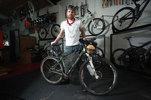 Justin Simoni and the single-speed bicycle he rode on the Tour Divide, now on display at Salvagetti Bicycle Workshop.