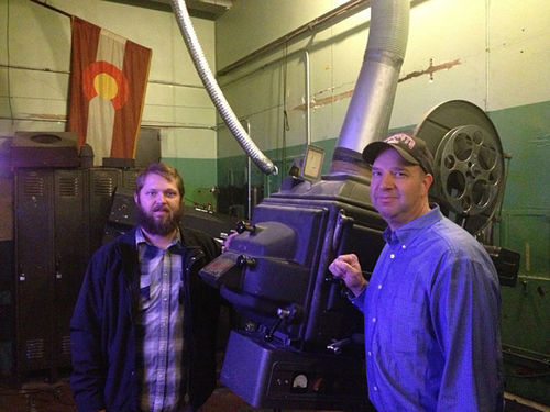 Ian Marzonie (left) and John Scheck of Kroenke with an old projector at the Paramount Theatre.