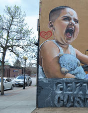 A father tattoos his three-year-old son in an eye-catching new mural