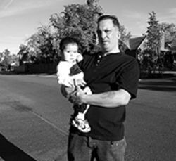 No notice: Brian Cordova, holding eighteen-month-old  Brian Jr., stands at the intersection where his mother  was fatally injured.