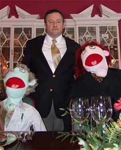 Skip Muller poses with the puppets that stood in for wealthy clients during butler training.