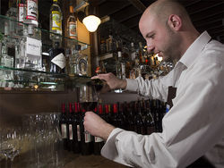 Georgos Reger pours wine at Axios. Slide show: In the kitchen at Axios Estiatorio
