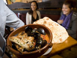 Michael Joyce delivers P.E.I. Mussels and Warm Flatbread to Salli Gutierrez and Marisol Landers. See the full slideshow from Salt the Bistro.
