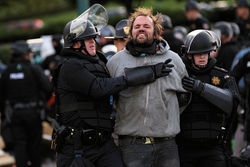 Denver police officers restrain Corey Donahue at Occupy Denver; he later smiled for a fresh mug shot.