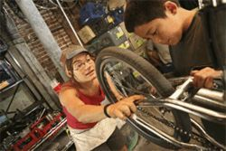 The wheels keep turning: Sarah Graves helps a  young cyclist fix his bike.