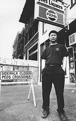 Taking a stand: Ung Hwa Choi outside his Larimer Street liquor store.