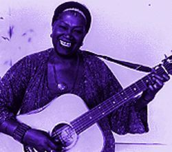 Smile, darn ya, smile: Odetta cradles her trusty guitar.