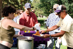 Food Not Bombs volunteer Raielle serves food to the homeless in Sunken Gardens Park.