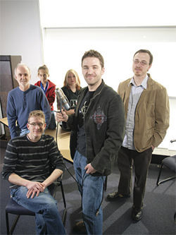 The volunteers behind Creative Music Works (clockwise from center): Andrew Starr (with microphone), Paul Riola, Ray Wentz, Naima Riola, Rhia Wisniewski, Matthew Garrington.