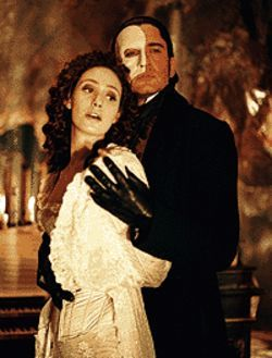 Gruesome, coosome twosome: Emmy Rossum and  Gerard Butler get cuddly in The Phantom of the  Opera.