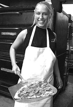 Hot stuff: Linda Pool shows off a pizza the action at  New York Pizzeria.