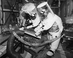 Moon-suited workers examine radioactive garbage.