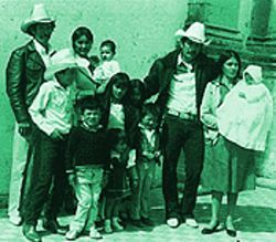 Mena posing for a family snapshot with his nine children, his wife and his brother.