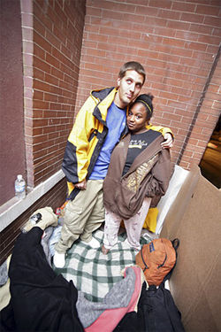 A.K. and Shantrell on the porch of 500 Park Avenue West, one of six vacant rowhouses owned by Welton Street Properties.